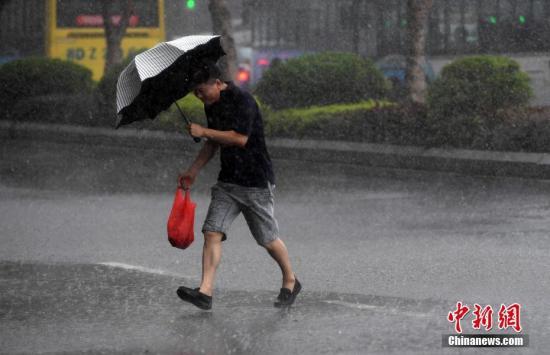 """8月25日,受台风""""白鹿""""影响,厦门遭遇大风暴雨。图为厦门市民在大雨中出行。 中新社记者 张斌 摄"""