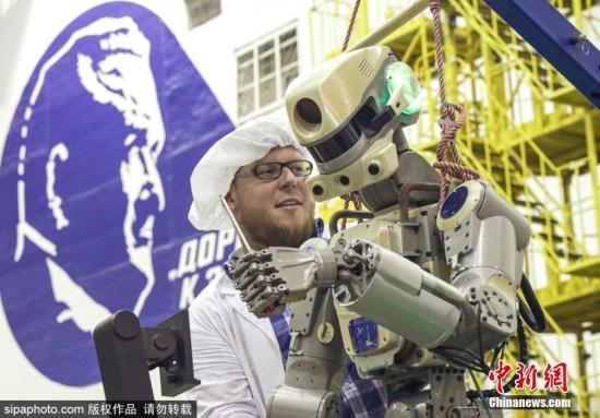 """当地时间8月27日,俄罗斯航天集团工作人员在控制室里工作。俄罗斯航天集团27日发布公告称,载有俄第一个太空机器人的""""联盟MS-14""""飞船与国际空间站二次对接成功。资料图为太空机器人为飞赴国际空间站做准备。图片来源:Sipaphoto 版权作品 禁止转载"""
