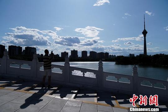 资料图:北京玉渊潭公园,一游客拍摄蓝天白云美景。中新社记者 张兴龙 摄