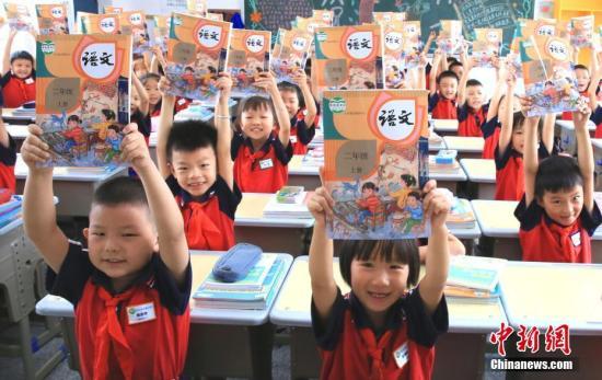 资料图:小学生领取新课本,迎接新学期。中新社发 司马天民 摄