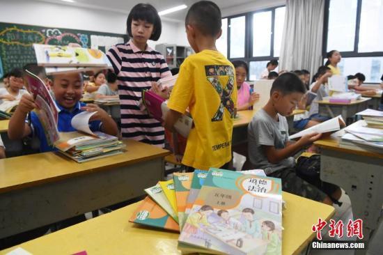 资料图:福州中山小学学生为同学发放教材。张斌 摄
