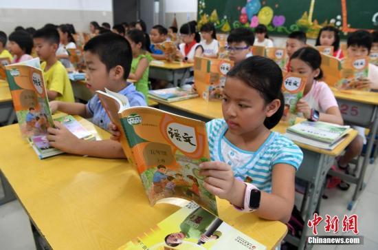 9月1日,福州中山小学五年级学生在阅读统一部编版的语文教材。(资料图片)张斌 摄