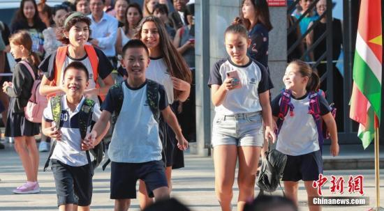9月1日,北京市朝阳区芳草地国际学校举行开学典礼,小学生们陆续走入校门。当日,北京市多所中小学正式开学。中新社记者 贾天勇 摄