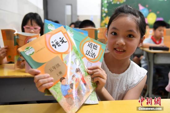 福州中山小学学生在展现发放的一致部编版的语文、品德与法治等教材。 张斌 摄