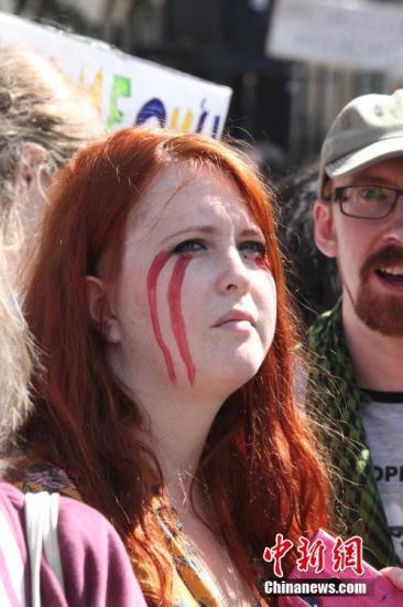 """8月31日,近万英国民众聚集在英国政府所在地伦敦唐宁街示威,抗议首相鲍里斯·约翰逊""""暂停议会""""。图为抗议人群中一""""流泪妆""""女子。/p中新社记者 张平 摄"""