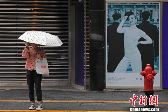 资料图:游客增加了衣物,等待过街。 殷立勤 摄