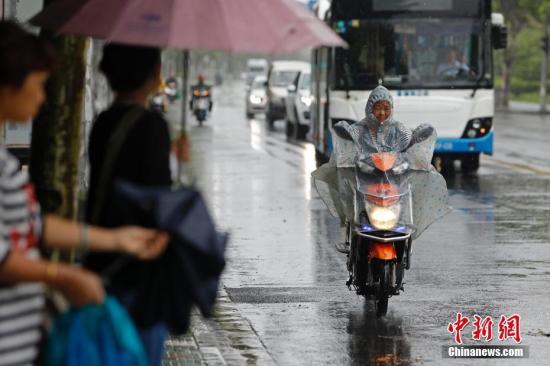 资料图:民众在雨中出行。殷立勤 摄