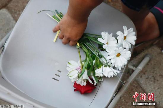 9月1日,在美国得克萨斯州敖德萨市,一名女子手握悼念遇难者的花束。