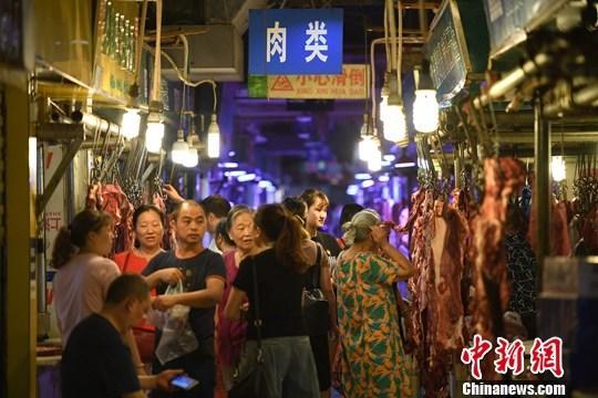 9月4日,重庆主城区的一家农贸市场内,市民挑选、购买牛肉。中新社记者 陈超 摄