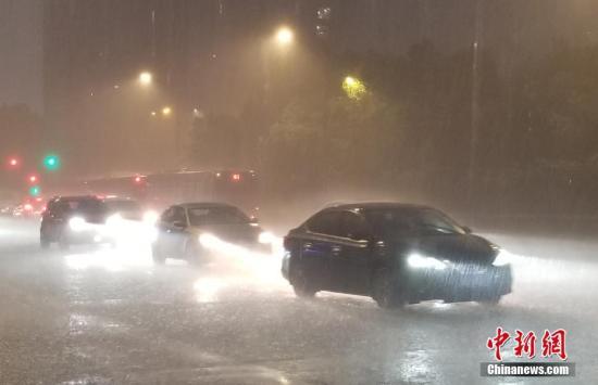 """9月5日,多辆轿车在大雨中行驶。当日,受今年第13号台风""""玲玲""""影响,浙江杭州部分区域突降大雨。中新社记者 王刚 摄"""