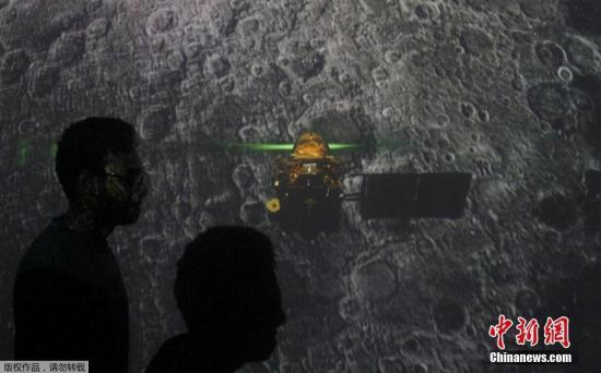 """当地时间9月7日,印度空间研究组织宣布,印度""""月船2号""""着陆器在距离月球表面2.1公里的时候失去了信号,该组织将分析数据找出原因。图为在孟买一所教育学院,学生们从""""月船2号""""着陆的直播大屏幕前走过。"""