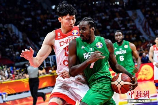 9月8日晚,中国队球员周琦(左)在比赛中防守尼日利亚球员阿米奴(中)的上篮。当晚,2019年国际篮联篮球世界杯17-32名排位赛继续进行,在广州举行的M组一场比赛中,中国(白)73比86不敌尼日利亚(绿)。<a target='_blank' href='http://wqru.cn/'>中新社</a>记者 陈骥旻 摄