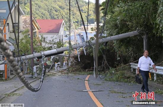 本地工夫9月9日,日本神奈川,须眉走过一条倾圮的电线杆。
