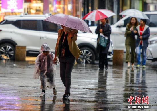 资料图:市民撑伞出行。 中新社记者 刘新 摄