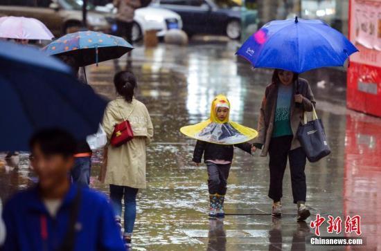 资料图:市民雨中出行。 中新社记者 刘新 摄