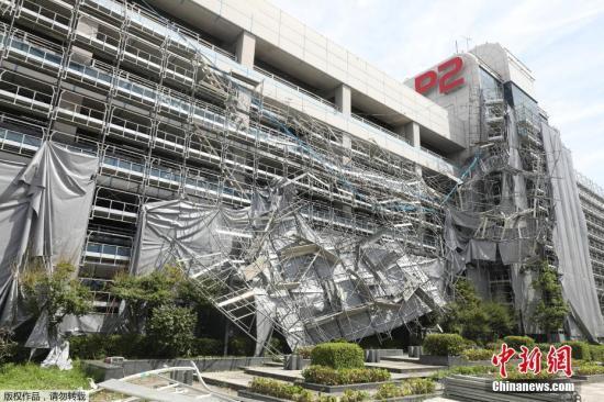 """据报道,日本首都圈9日遭遇今年第15号台风""""法茜""""直接袭击,东日本铁路公司(JR东日本)的普通铁路从始发列车开始实施大规模停运,交通网出现混乱,至少约120万人受到影响。灾情陆续出现,导致至少3人死亡,约50人受伤。此外,输电线路铁塔倒塌等导致约93万户停电。图为羽田机场车库的临时脚手架坍塌。"""