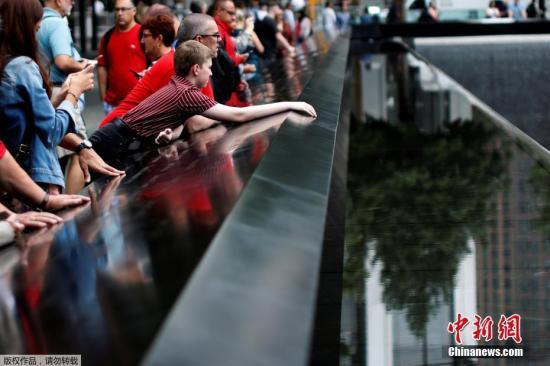 """当地时间9月10日,美国""""9·11""""恐怖袭击事件18周年纪念日即将到来之际,在纽约""""9·11""""遗址纪念广场,民众在纪念碑旁悼念遇难者。"""
