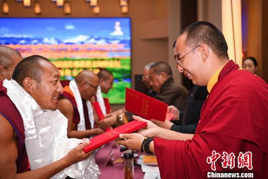 """9月10日,中国佛教协会西藏分会第四届藏传佛教教义阐释论坛暨坚持藏传佛教中国化方向研讨会在日喀则市举行。论坛围绕""""修行在于利众""""主题,130名高僧大德撰写了134篇阐释论文,20位高僧大德在论坛上作了阐释演讲。图为全国政协常委、中国佛协副会长、中国佛协西藏分会会长班禅额尔德尼•确吉杰布(右)为优秀阐释论文作者颁奖。中新社记者 何蓬磊 摄"""