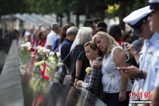 """資料圖:美國""""9·11""""恐怖襲擊事件紀念活動在紐約""""9·11""""遺址紀念廣場舉行。民眾在紐約世貿遺址前寄哀思。<a target='_blank' href='http://www.woodcuttr.com/'>中新社</a>記者 廖攀 攝"""
