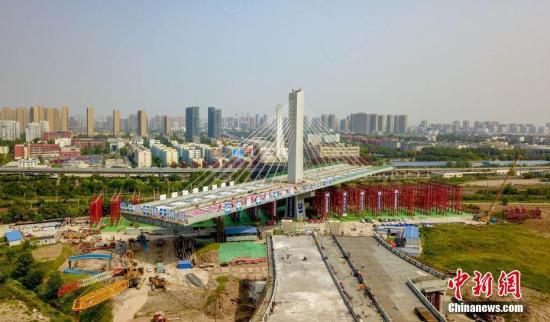 """9月11日,长248米、重1.8万吨的武汉杨泗港快速通道青菱段斜拉桥在8号墩带动下,平稳地逆时针转体77度后,与此前一天旋转了105度、同等长度和重量的9号墩成功""""牵手""""。至此,这座世界上跨度最大、桥面最宽的转体斜拉桥基本建成。武汉杨泗港快速通道青菱斜拉桥是长江上首座双层公路——杨泗港长江大桥的重要配套工程。斜拉桥全长508米,标准宽度44米,最宽处达46米,是当今世界跨度最大、桥面最宽的转体桥,还是世界上首座独柱塔钢箱梁半漂浮体系转体斜拉桥。图为斜拉桥进行转体作业。 中新社记者 郑子颜 摄"""