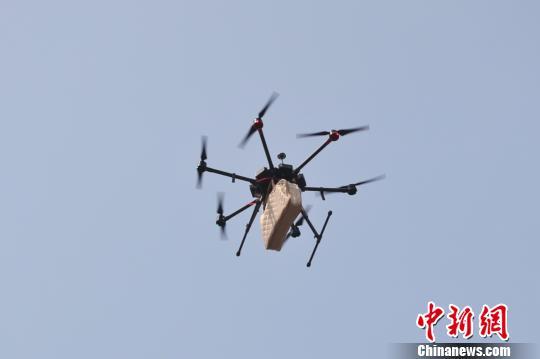 一架6旋翼无人机载着一条羽绒被向纪录发起挑战。 张亨伟 摄