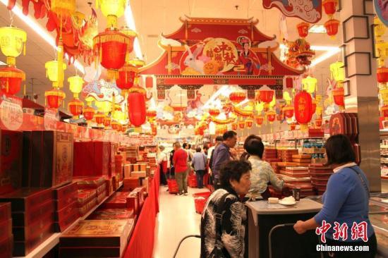 """当地时间9月12日,中秋节来临之际,加拿大多伦多一家华人超市的""""月饼街""""颇为热闹,琳琅满目的各式月饼吸引顾客驻足选购。/p中新社记者 余瑞冬 摄"""