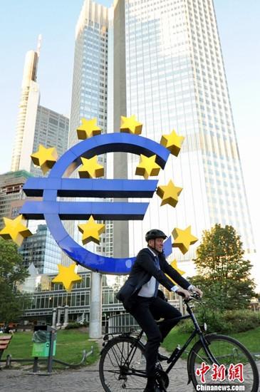 """9月12日,坐落德国法兰克福的欧洲央行正式宣告降息决议,将欧元区隔夜存款利率下调10个基点至负0.50%。一起,欧洲央行还宣告从11月1日起重启财物购买方案(即QE,量化宽松),规划为每月200亿欧元。图为路人当天下午经过法兰克福市中心""""欧元塔""""前的欧元造型雕塑。中新社记者 彭大伟 摄"""