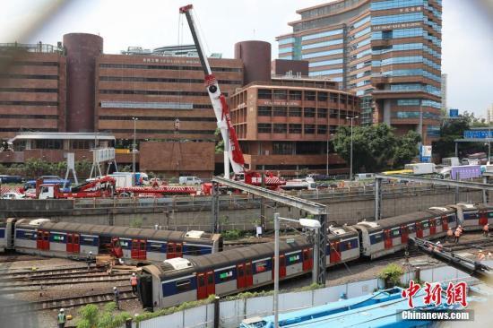 9月17日,香港港铁红磡站早上约8时30分发作列车越轨事端,车厢断开两截,有车门飞脱,消防证明至少有8人受伤。图为港铁出动大型吊车对越轨列车进行抢修。 记者 谢光磊 摄