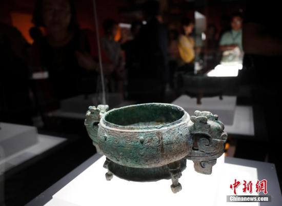 """9月17日,文化和旅游部、国家文物局主办的""""回归之路——新中国成立70周年流失文物回归成果展""""在中国国家博物馆开幕。中国国家文物局系统梳理了中华人民共和国成立70年来300余批次、15万余件回归文物情况,精心遴选25个具有代表性的文物回归案例,统筹调集全国12个省市、18家文博单位的600余件文物参展,这是中国首次对流失文物回归工作进行全景式展现。图为观众参观范季融捐赠青铜器文物。 中新社记者 杜洋 摄"""
