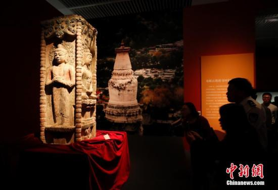 """9月17日,文化和旅游部、国家文物局主办的""""回归之路——新中国成立70周年流失文物回归成果展""""在中国国家博物馆开幕。中国国家文物局系统梳理了中华人民共和国成立70年来300余批次、15万余件回归文物情况,精心遴选25个具有代表性的文物回归案例,统筹调集全国12个省市、18家文博单位的600余件文物参展,这是中国首次对流失文物回归工作进行全景式展现。图为观众参观邓峪石塔塔身。 中新社记者 杜洋 摄"""