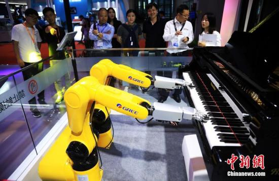 """9月18日,""""钢琴机器人""""现场演奏,吸引观众。据介绍,该工业机器人搭配仿生灵巧手,实现机器人弹钢琴,让工业与艺术得以融合。正在国家会展中心(上海)举行的第21届中国国际工业博览会,以""""智能、互联——赋能产业新发展""""为主题,共设9大专业展,集中展示智能、互联驱动下的产业发展新成效以及工业最新技术、产品和服务,来自27个国家和地区的2600多家企业参展。中新社记者 汤彦俊 摄"""