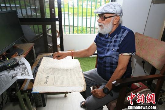 中新社记者日前采访75岁的德文德拉·高塔姆(Devendra Gautam)。重新打开自己主持创办的《尼泊尔邮报》,泛黄且有所破损的纸张让德文德拉·高塔姆忆起年轻时的激情岁月。图为在位于加德满都谷地外的郊区、德文德拉·高塔姆的居所内,德文德拉•高塔姆翻看《尼泊尔邮报》(创刊号)。中新社记者 张晨翼 摄
