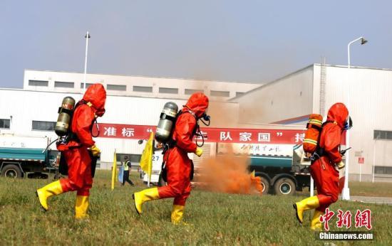 9月19日,湖北省咸宁市举行应急救援综合拉动演练。演练设定当地一厂区内1号成品仓库有大量浓烟,并有人员被困。现场,消防员利用沙袋对灾害事故现场核心区域进行筑堤堵截。同时,指挥部调集卫健、交通、环保、城管、气象、供电、电信等部门应急救援力量和应急装备到场增援,协同作战。此次演练旨在检验咸宁应急救援综合协调能力、科学决策能力、迅速反应能力和信息化集成能力,提升应对重大突发事件处置能力。 朱燕林 摄