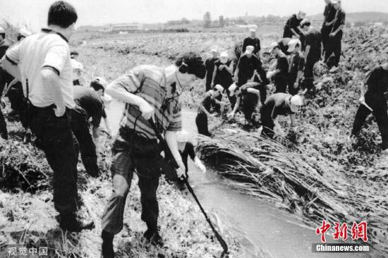 1993年7月,韩国华城连环杀人案调查人员在一条水沟里寻找遗物。图片来源:视觉中国