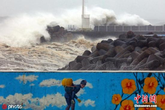 """当地时间9月22日,今年第17号台风""""塔巴""""于当日早晨登陆韩国,狂风掀起,巨浪拍岸,海面波涛汹涌。图片来源:ICphoto"""
