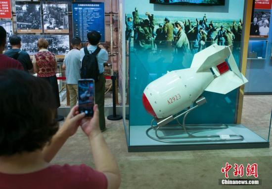 """9月24日,""""伟大历程 辉煌成就——庆祝中华人民共和国成立70周年大型成就展""""在北京展览馆向公众开放。图为参观者拍摄新中国第一颗原子弹模型。中新社记者 侯宇 摄"""