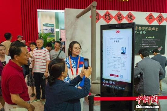 """9月24日,""""巨大进程 辉煌成果——庆祝中华人民共和国建立70周年大型成果展""""在北京展览馆向大众敞开。图为参观者体会制造高考""""准考证""""。记者 侯宇 摄"""