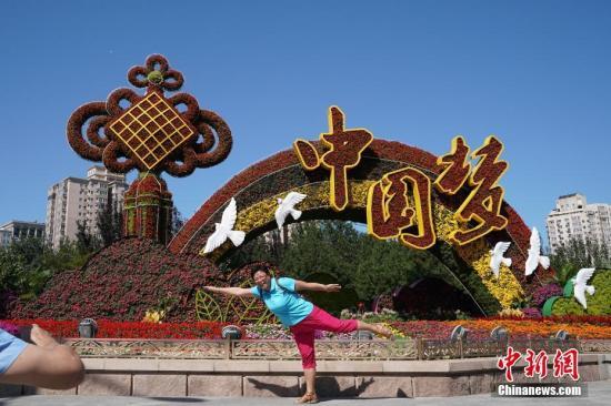 材料图:气候阴沉,市平易近正在主题花坛前摄影纪念。a target='_blank' href='http://www.chinanews.com/'中新社/a记者 张兴龙 摄