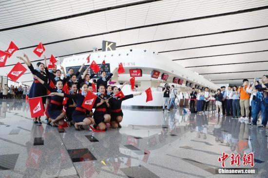 9月25日16时20分许,7架大型客机顺次从跑道起飞,标志着北京大兴国际机场正式通航。图为中联航地服人员在大兴机场进行快闪扮演。记者 殷立勤 摄