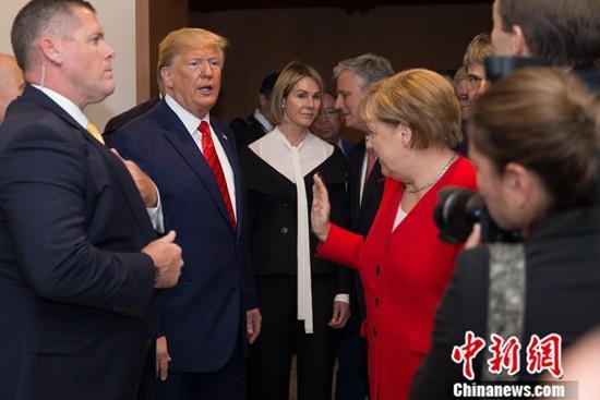 资料图:美国总统特朗普与德国总理默克尔进行交流。/p中新社记者 廖攀 摄