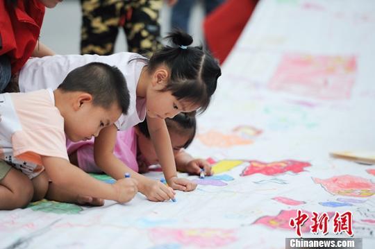 9月26日,小朋友们在长卷上进行绘画。当日,安徽合肥平塘王村辖区幼儿园开展主题亲子绘长卷活动,迎接国庆。中新社发 王家国 摄
