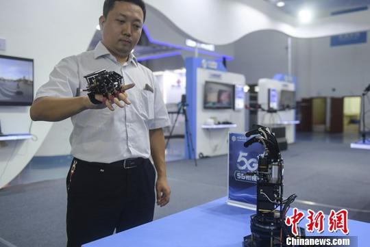 """9月27日,市民体验""""5G机械臂""""性能。当日,在第十二届济南国际信息技术博览会上,运用5G技术操控的机器人、机械臂,吸引观众参观、体验。中新社记者 张勇 摄"""