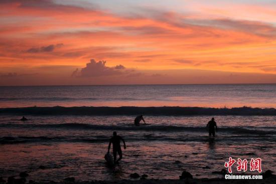 夕阳西下,在海边的冲浪者。图片来源:视觉中国
