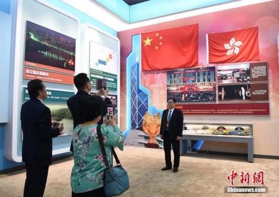 """图为侨胞在""""香港回归""""展区拍照留念。<a target='_blank' href='http://www.chinanews.com/'>中新社</a>记者 侯宇 摄"""
