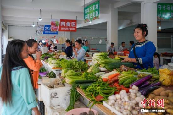 资料图:贵州省一易地扶贫搬迁安置点居民在菜市场卖菜。中新社记者 贺俊怡 摄