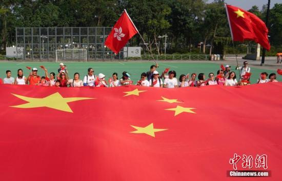 """9月29日上午,一群香港市民来到维多利亚公园参加欢度国庆快闪活动,共同展示一面长15米的巨幅五星红旗,高唱爱国歌曲《歌唱祖国》等,并高喊""""中华人民共和国万岁,我们永远都是护旗手!""""等口号。<a target='_blank' href='http://www.nihaopiao.com/'>中新社</a>记者 张炜 摄"""