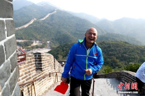 """9月30日,香港警队代表来到北京八达岭长城参观游览。近日,10位受邀参加国庆70周年庆祝活动的香港警队代表抵达北京。图为香港警务处机动部队警署警长、被称为""""光头警长刘Sir""""的刘泽基登八达岭长城。中新社记者 富田 摄"""