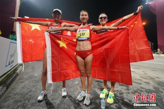图为刘虹(中)、切阳什姐(右)和杨柳静(左)手持国旗庆祝。中新社记者 泱波 摄