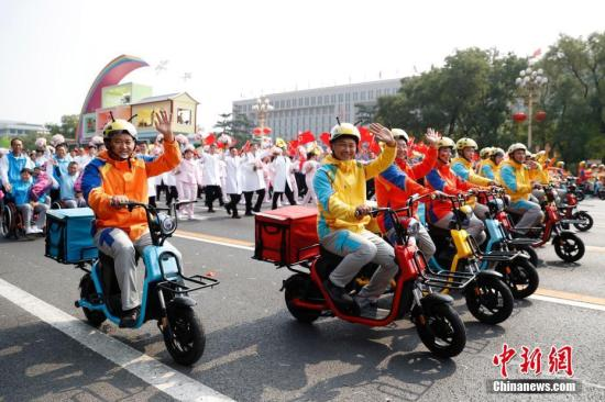 """10月1日上午,庆祝中华人民共和国成立70周年大会在北京天安门广场隆重举行。图为群众游行中的""""快递小哥""""。中新社记者 韩海丹 摄"""