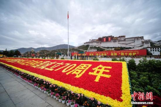 """10月1日上午,西藏自治区在布达拉宫广场举行""""升国旗、唱国歌""""仪式,庆祝中华人民共和国成立70周年。中新社记者 何蓬磊 摄"""